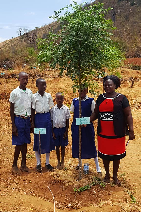Principal and her pupils showing their mukau tree